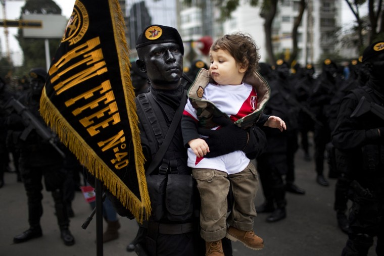 Intor Montoro Carba, 20, a military special forces officer, holds Jeremy Bock, at the request of Jeremy's parents who wanted to make a photo of their son with the striking soldier, before the start of a military parade marking the country's Independence Day in Lima, Peru, Friday, July 29, 2016. Peru declared it's independence from Spain in 1821. (AP Photo/Rodrigo Abd)