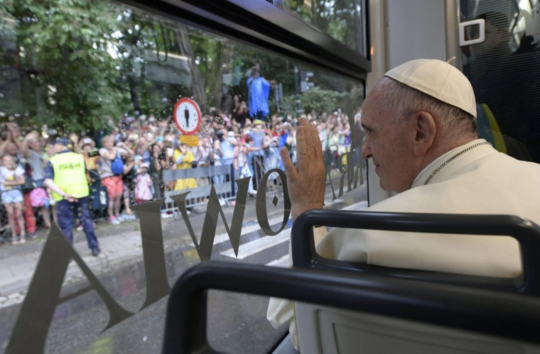 Pope Francis waves to faithful from a tram window on his way to Krakow's Jordan Park, Poland. (Osservatore Romano/Pool Photo via AP)