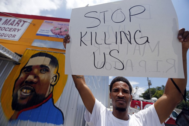 A man holds a sign in front of a mural of Alton Sterling while attorneys, not pictured, speak in front of the Triple S Food Mart in Baton Rouge, La., Thursday, July 7, 2016. Sterling, 37, was shot and killed outside the convenience store by Baton Rouge police, where he was selling CDs. (AP Photo/Gerald Herbert)