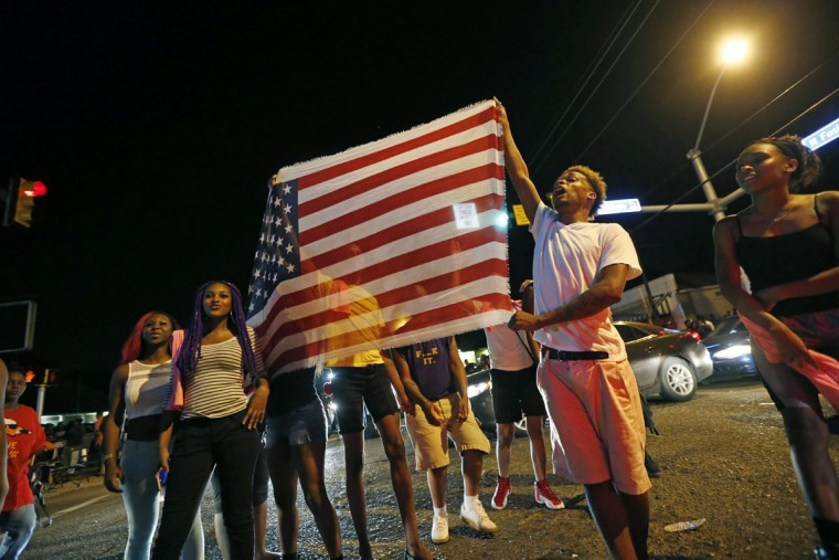 "Protestors carry an American flag chanting ""all lives matter"" as they congregate at N. Foster Dr. and Fairfields Ave., the location of the Triple S convenience store in Baton Rouge, La., Wednesday, July 6, 2016. Alton Sterling, 37, was shot and killed outside the store by Baton Rouge police, where he was selling CDs. (AP Photo/Gerald Herbert)"