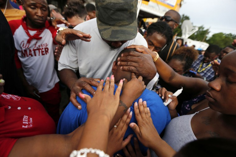 Cameron Sterling, son of Alton Sterling, is comforted by hands from the crowd at a vigil outside the Triple S convenience store in Baton Rouge, La., Wednesday, July 6, 2016. Alton Sterling, 37, was shot and killed by Baton Rouge police outside the store where he was selling CDs. (AP Photo/Gerald Herbert)