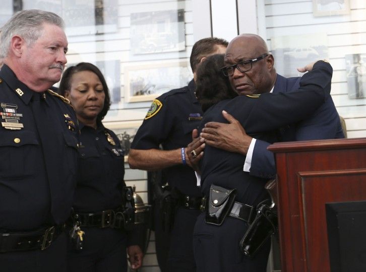 Acting Houston Police Chief Martha Montalvo hugs Bishop James Dixon after a prayer vigil at the Houston Police Department, Friday, July 8, 2016, in Houston, in response to five police officers who were fatally shot during what began as a peaceful protest in Dallas the night before. (Elizabeth Conley/Houston Chronicle via AP)