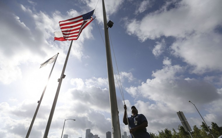 Al Smith, a city of Houston employee, lowers the flags in front of the Houston Police Memorial at Memorial Park to half staff, Friday, July 8, 2016, in Houston, in response to five police officers who were fatally shot during what began as a peaceful protest in Dallas the night before. (Elizabeth Conley/Houston Chronicle via AP)