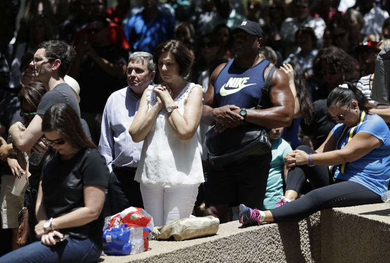People take part in a prayer vigil at Thanksgiving Square, Friday, July 8, 2016, in Dallas. Five police officers are dead and several injured following a shooting during what began as a peaceful protest in the city the night before. (AP Photo/Eric Gay)