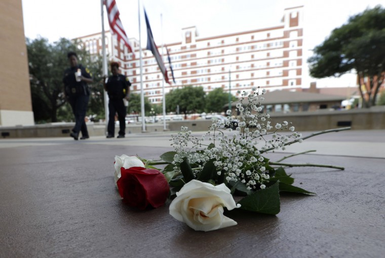 Dallas Police officers walk past roses left at the front doors of the station as part of a makeshift memorial, Friday, July 8, 2016, in Dallas. Five police officers are dead and several injured following a shooting during what began as a peaceful protest in the city the night before. (AP Photo/Eric Gay)