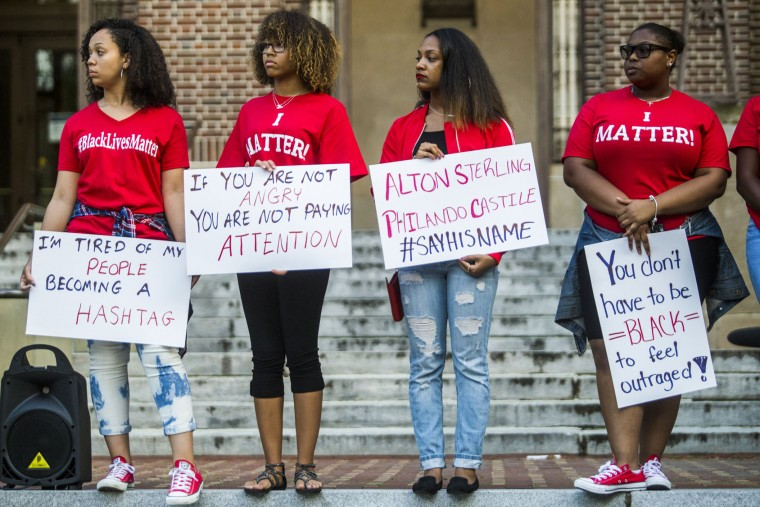 In this photo taken Thursday, July 7, 2016, women hold up signs during a vigil at the University of Michigan Diag in Ann Arbor, Mich., in honor of Alton Sterling and Philando Castile, two black men recently shot and killed by police. (Katy Kildee/The Ann Arbor News via AP)