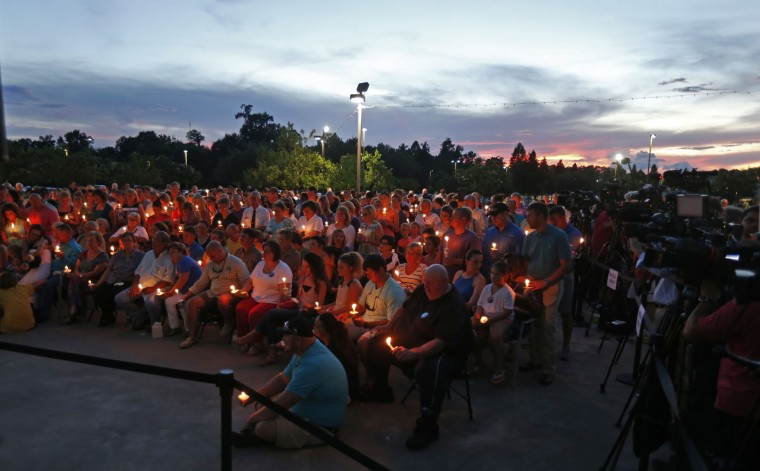 People attend a candlelight vigil for the fallen Baton Rouge police officers at the Healing Place Church in Baton Rouge, La., Monday, July 18, 2016. Multiple police officers were killed and wounded Sunday morning in a shooting near a gas station in Baton Rouge. (AP Photo/Gerald Herbert)