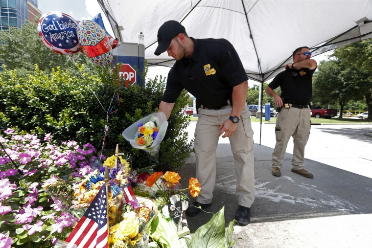 A police officer places flowers, handed to him by a motorist, outside Our Lady of the Lake Medical Center, where slain and wounded police officers were taken, in Baton Rouge, Monday, July 18, 2016. Multiple police officers were killed and wounded Sunday morning in a shooting near a gas station in Baton Rouge, less than two weeks after a black man was shot and killed by police here, sparking nightly protests across the city. (AP Photo/Gerald Herbert)