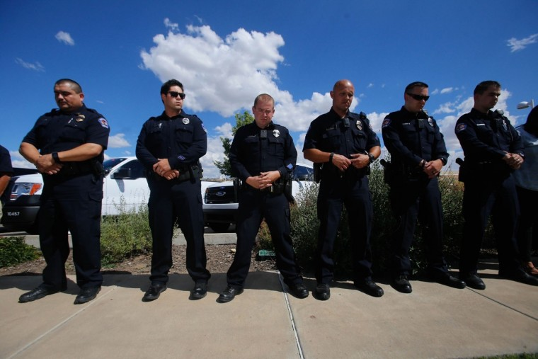 In this Monday, July 18, 2016 photo, Members of the Farmington Police Department bow their heads during a moment of silence outside the Farmington, N.M., Museum at Gateway Park. The department organized five minutes of silence to honor the officers injured and killed Sunday in Baton Rouge, La. (Jon Austria/The Daily Times via AP)