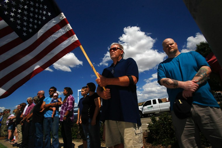 In this Monday, July 18, 2016 photo, Ernest Vaughn holds a flag, during a vigil for the officers killed in Baton Rouge, La. , at the Farmington Museum at Gateway Park in Farmington, N.M. (Jon Austria/The Daily Times via AP)