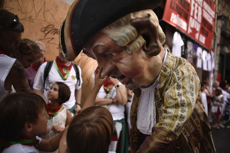 A young boy touches the nose of a ''Cabezudo'', a member of the San Fermin Comparsa Parade, during a religious procession at the San Fermin Festival, in Pamplona, northern Spain, Thursday, July 7, 2016. Revelers from around the world arrive in Pamplona every year to take part in some of the eight days of the running of the bulls. (AP Photo/Alvaro Barrientos)