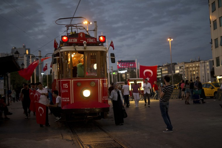 People hold Turkish flags by tram in Taksim Square in Istanbul, as government supporters protest, Monday, July 18, 2016. Turkey's Interior Ministry has fired nearly 9,000 police officers, bureaucrats and others and detained thousands of suspected plotters following a foiled coup against the government, Turkey's state-run news agency reported Monday. (AP Photo/Petros Giannakouris)