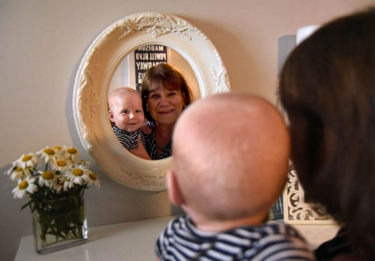 Terry Hewitt brings her grandson Ollie to a mirror where they can make smiling faces together. She said the triplets look a lot like their dad when he was a baby. (Amy Davis/Baltimore Sun)