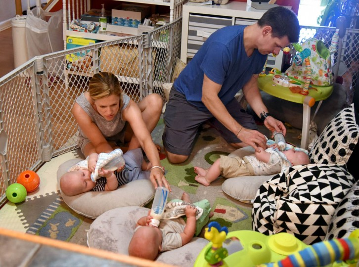 The triplets, clockwise from left, Ollie, Trip and Finn, can now hold their own bottles, but still need supervision from parents Kristen and Thomas Hewitt Jr. (Amy Davis/Baltimore Sun)