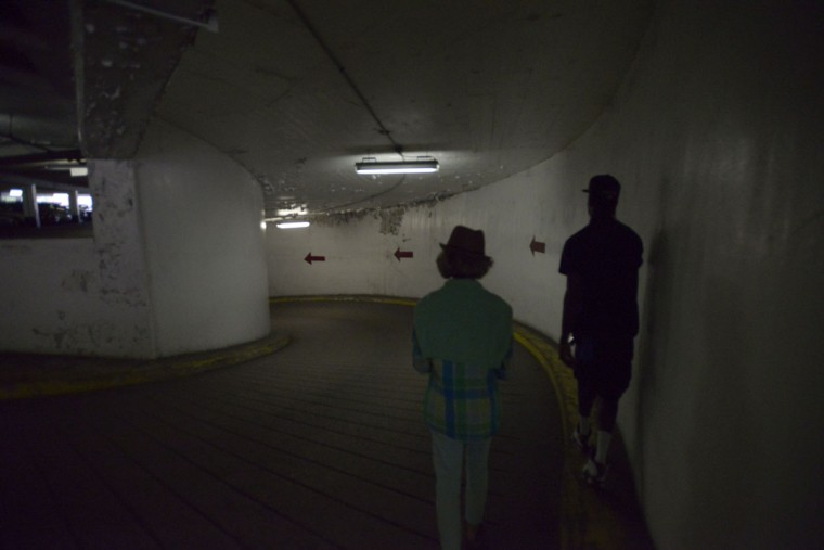 We're doing this. We're going into the abandoned nightclub beneath Lexington Market. Darlene Hudson leads the way and Darelle Miller holds the flashlight. (Christina Tkacik/Baltimore Sun)