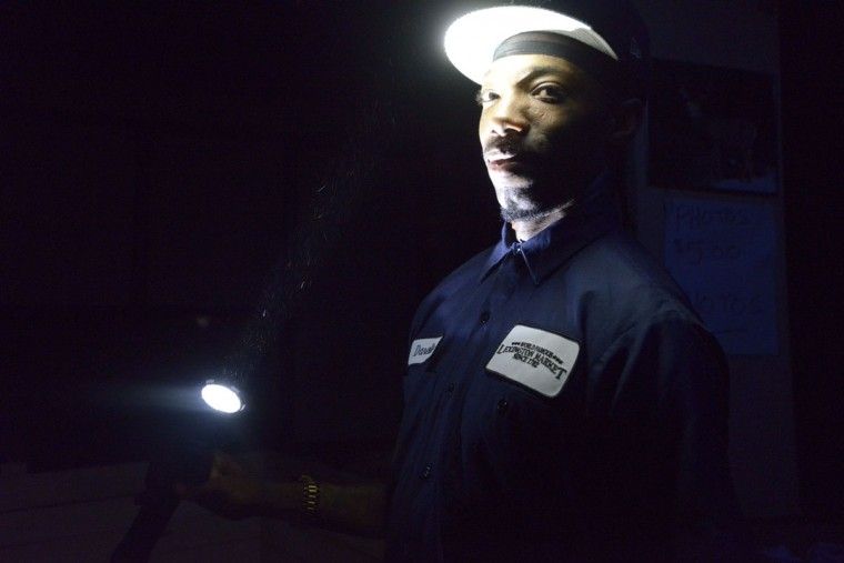 Darelle Miller, a maintenance worker at Lexington Market, holds a flashlight in the unlit dungeon. (Christina Tkacik/Baltimore Sun)