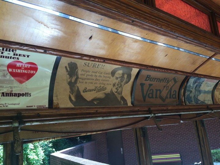 Antique advertisements and a warning line the ceiling of an old streetcar from 1902, reminding riders of a previous era. (Christina Tkacik/Baltimore Sun)