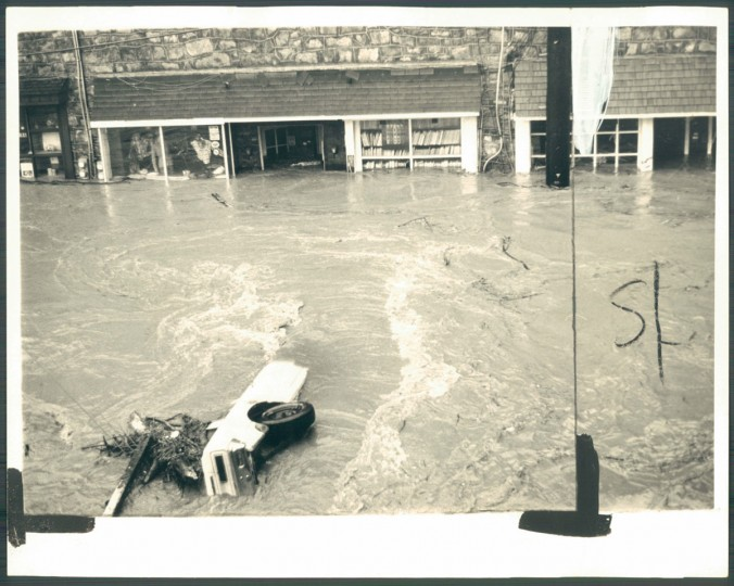Ellicott City's Main street is awash with floodwaters and debris including this car which was caught in the currents on the outskirts of town near the Frederick road bridge. September 27, 1975.