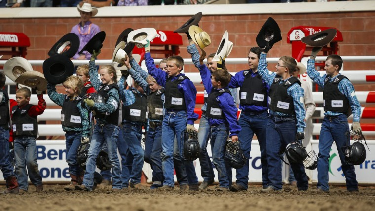 Young cowgirls and cowboys salute the crowd after competing in the wild pony race during the Calgary Stampede in Calgary, Alberta, Sunday, July 10, 2016. (Jeff McIntosh/The Canadian Press via AP)