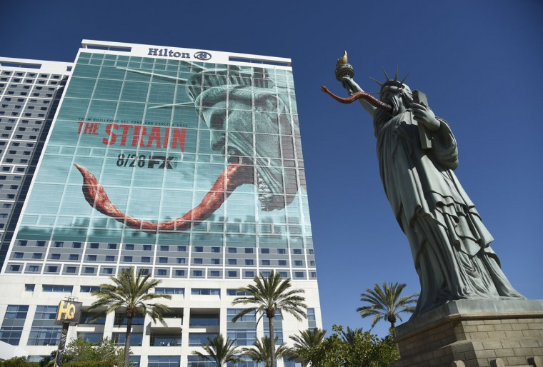"A Statue of Liberty character from ""The Strain"" appears next to an advertisement for the show on the Hilton Bayfront hotel on day 1 of Comic-Con International on Thursday, July 21, 2016, in San Diego. (Photo by Chris Pizzello/Invision/AP)"