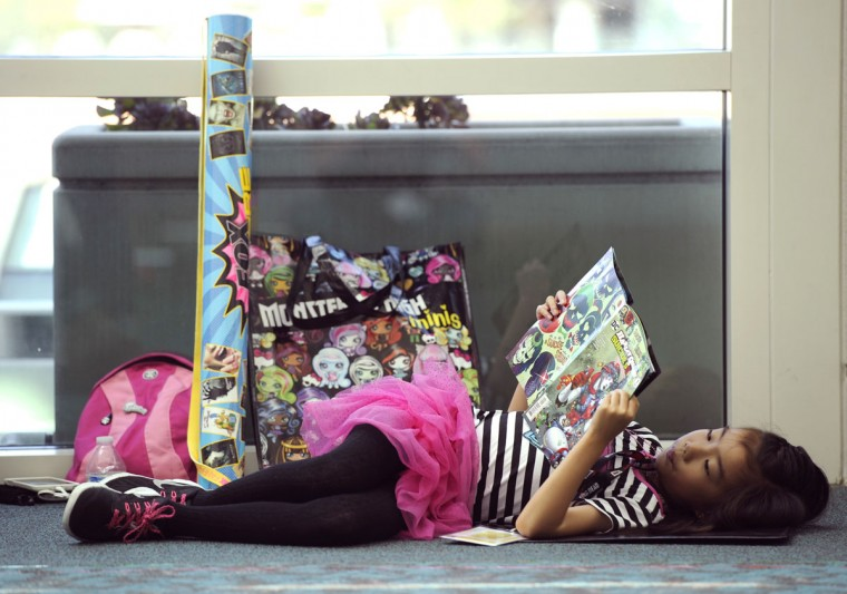 "Jadelyn Chu, 8, of San Diego, reads a ""Suicide Squad"" comic book while lying on the convention center floor on day 1 of Comic-Con International on Thursday, July 21, 2016, in San Diego. (Photo by Chris Pizzello/Invision/AP)"