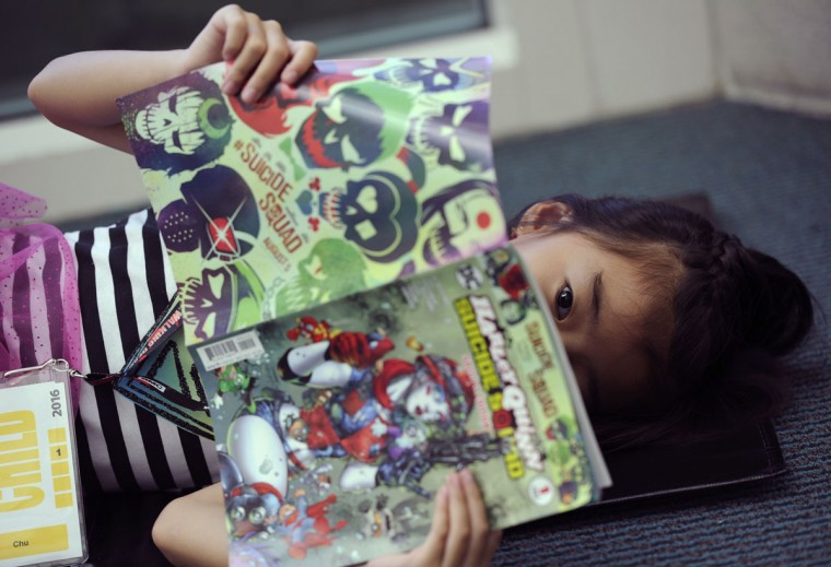 "Jadelyn Chu, 8, of San Diego, reads a ""Suicide Squad"" comic book on the Convention Center floor on day 1 of Comic-Con International on Thursday, July 21, 2016, in San Diego. (Photo by Chris Pizzello/Invision/AP)"
