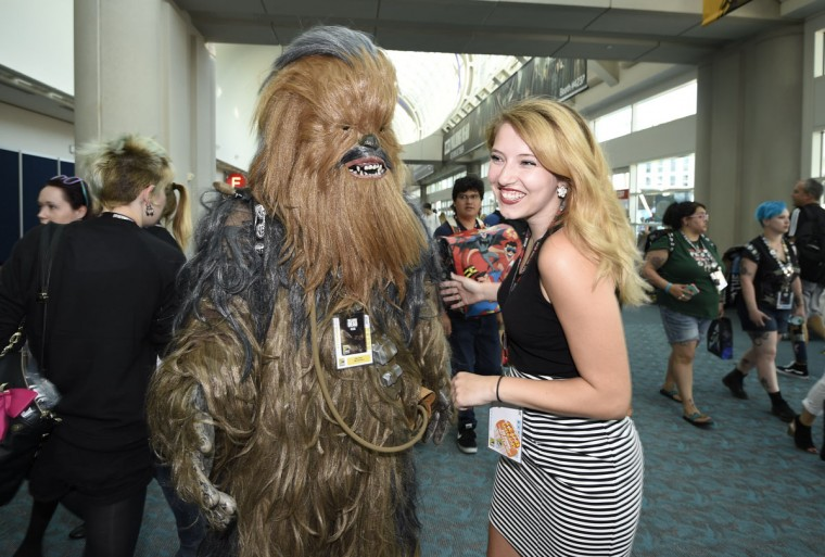 "Michael Muhlestein, dressed as the ""Star Wars"" character, Chewbacca, jokes with Candice Heath on day one of Comic-Con International held at the San Diego Convention Center Thursday, July 21, 2016, in San Diego. (Photo by Denis Poroy/Invision/AP)"