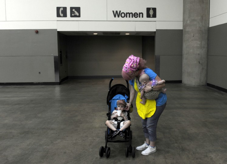 "Holding her daughter Jenna, 3 months, Tiffany Hendren of Wilson, North Carolina rubs her son Jacob's ears. Jacob is two and a half. ""I like dressing up,"" Hendren said. ""I like the show."" BronyCon is the world's largest My Little Pony: Friendship is Magic convention. Held at the Baltimore Convention Center, BronyCon features panels, meet-ups, activities, and cosplay. (Caitlin Faw/Baltimore Sun staff)"