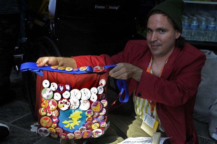 "Josh Van from Albuquerque, New Mexico shows off his bag covered with buttons and pins he's collected at other conventions and on the Internet. This is Van's third BronyCon convention. ""I come back for the vendors, people, and panels. It's a really good experience. I met a lot of friends here."" BronyCon is the world's largest My Little Pony: Friendship is Magic convention. Held at the Baltimore Convention Center, BronyCon features panels, meet-ups, activities, and cosplay. (Caitlin Faw/Baltimore Sun staff)"