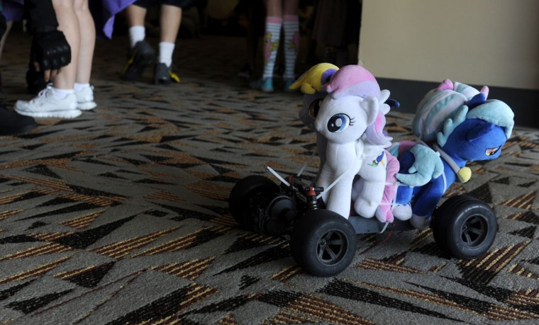"Garrick Gorden of Omaha, Nebraska constructed a pony mobile. Pony plushies are tied to an RC car. ""People's reactions to it are pretty cool,"" Gorden said. BronyCon is the world's largest My Little Pony: Friendship is Magic convention. Held at the Baltimore Convention Center, BronyCon features panels, meet-ups, activities, and cosplay. (Caitlin Faw/Baltimore Sun staff)"