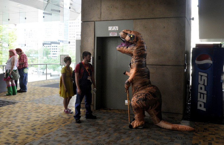 A dinosaur waits for the elevator. BronyCon is the world's largest My Little Pony: Friendship is Magic convention. Held at the Baltimore Convention Center, BronyCon features panels, meet-ups, activities, and cosplay. (Caitlin Faw/Baltimore Sun staff)