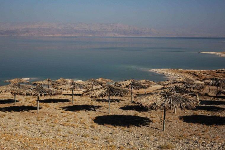 A general view shows umbrellas on a beach on the shore of the Dead Sea after it was abandoned following the appearance of sinkholes in Ein Gedi tourist resort in Israel on July 11, 2016. (MENAHEM KAHANA/AFP/Getty Images)