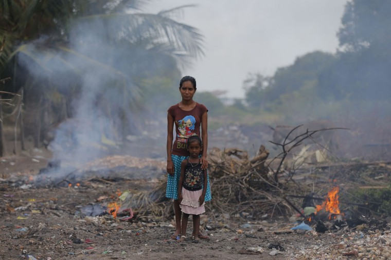 In this July 18, 2016 photo, a Sri Lankan woman and a child from a fishing family stand in the rising smoke from burning litter in a destroyed mangrove area in Kalpitiya, about 130 kilometers (81 miles) north of Colombo, Sri Lanka. Sri Lanka's government and environmentalists are working to protect tens of thousands of acres of mangrove forests _ the seawater-tolerant trees that help protect and build landmasses, better absorb carbon from the environment mitigating effects of global warming and reducing impact of natural disasters like tsunamis. Authorities have identified about 37,000 acres (15,000 hectares) of mangrove forests in Sri Lanka that are earmarked for preservation. (AP Photo/Eranga Jayawardena)