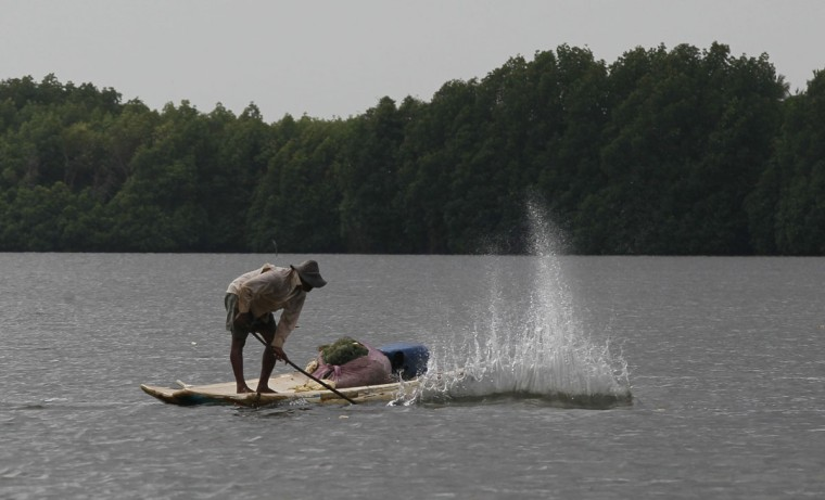 In this July 15, 2016 photo, a Sri Lankan small scale fisherman agitates the water surface before fishing in Pambala, about 70 kilometers (44 miles) north of Colombo, Sri Lanka. Sri Lanka's government and environmentalists are working to protect tens of thousands of acres of mangrove forests _ the seawater-tolerant trees that help protect and build landmasses, better absorb carbon from the environment mitigating effects of global warming and reducing impact of natural disasters like tsunamis. Authorities have identified about 37,000 acres (15,000 hectares) of mangrove forests in Sri Lanka that are earmarked for preservation. (AP Photo/Eranga Jayawardena)