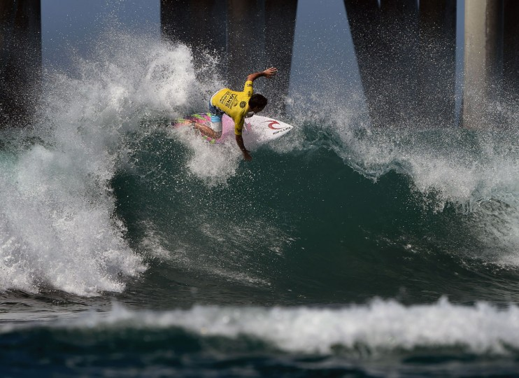 Mason Ho of Hawaii surfs beside the pier in his men's heat during the first round of the US Open of Surfing at Huntington Beach, California on July 25, 2016. (MARK RALSTON/AFP/Getty Images)