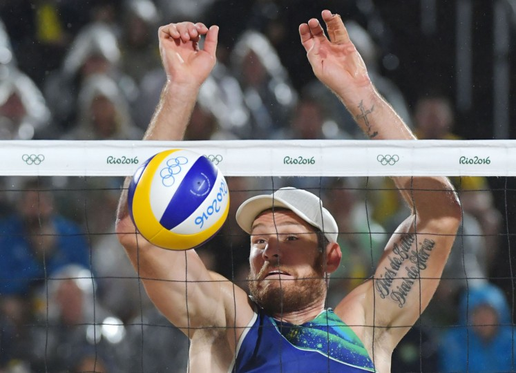 Brazil's Alison Cerutti eyes the ball during the men's beach volleyball final match between Italy and Brazil at the Beach Volley Arena in Rio de Janeiro late on August 18, 2016, for the Rio 2016 Olympic Games. (Yasuyoshi Chiba/AFP/Getty Images)