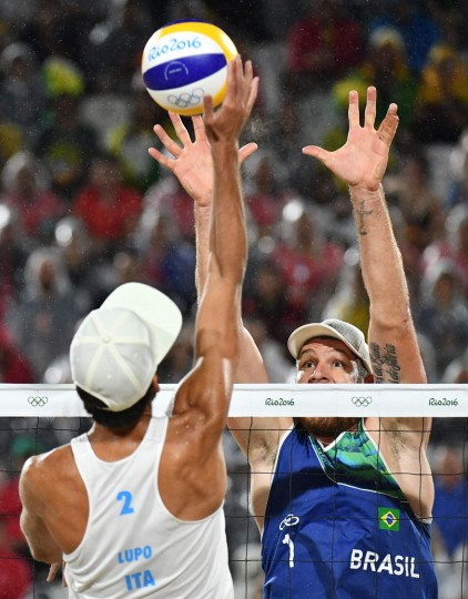 Italy's Daniele Lupo (L) spikes the ball during the men's beach volleyball final match between Italy and Brazil at the Beach Volley Arena in Rio de Janeiro late on August 18, 2016, for the Rio 2016 Olympic Games. (Leon Neal/AFP/Getty Images)