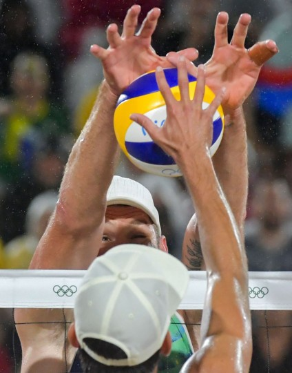 Brazil's Alison Cerutti (back) tries to block the ball during the men's beach volleyball final match between Italy and Brazil at the Beach Volley Arena in Rio de Janeiro late on August 18, 2016, for the Rio 2016 Olympic Games. (Yasuyoshi Chiba/AFP/Getty Images)