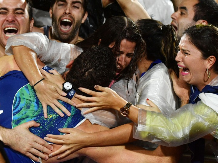 Brazil's Alison Cerutti (C) celebrates after winning the men's beach volleyball final match between Italy and Brazil at the Beach Volley Arena in Rio de Janeiro late on August 18, 2016, for the Rio 2016 Olympic Games. (Leon Neal/AFP/Getty Images)