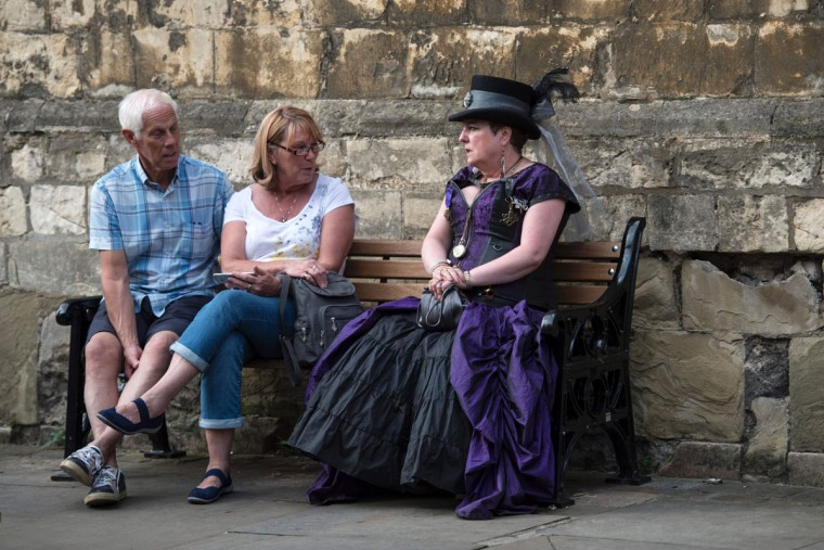 A Steampunk enthusiast sits on a bench on the first day of 'The Asylum Steampunk Festival' in Lincoln, northern England on August 26, 2016. The four-day alternative lifestyle festival is the largest and longest running steampunk festival in the World; combining art, literature, music, fashion and comedy. Steampunk is a subgenre of science fiction or science fantasy that incorporates technology and aesthetic designs inspired by 19th-century industrial steam-powered machinery. / (AFP Photo/Oli Scarff)