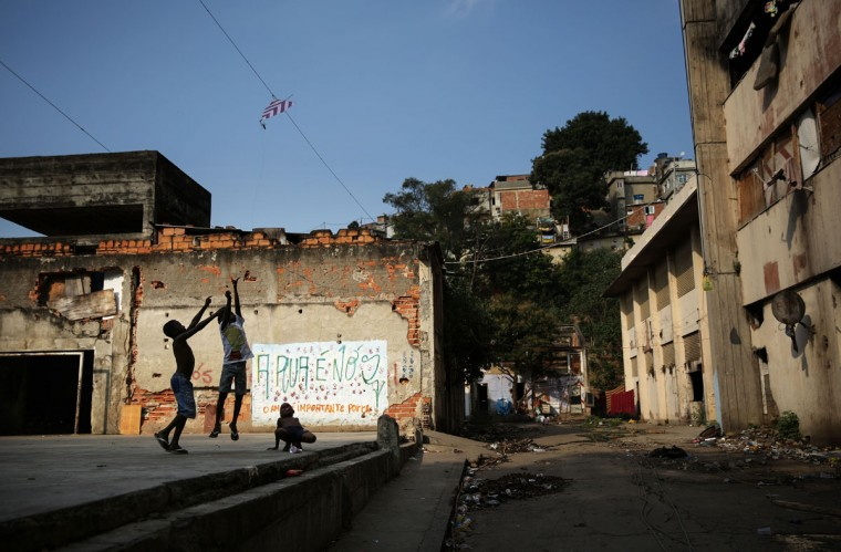 RIO DE JANEIRO, BRAZIL - AUGUST 09: Children try to pull down a kite caught on a line outside an occupied building in the Mangueira 'favela' community on August 9, 2016 in Rio de Janeiro, Brazil. Hundreds of residents who live in the surrounding structures must collect water from hoses as there is no running water in the buildings. Much of the Mangueira 'favela' community sits about a kilometer away from Maracana stadium, the site of the opening and closing ceremonies for the Rio 2016 Olympic Games. The stadium has received hundreds of millions of dollars in renovations ahead of the World Cup and Olympics. The Morar Carioca plan to urbanize Rio's favelas, or unplanned settlements, by 2020, was one key social legacy project heralded ahead of the Rio 2016 Olympic Games. The plan has mostly failed to materialize. Around 1.4 million residents, or approximately 22 percent of Rio's population, reside in favelas which often lack proper sanitation, health care, education and security due to gang and police violence. (Photo by Mario Tama/Getty Images)