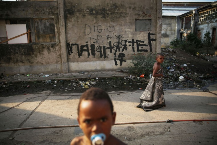 RIO DE JANEIRO, BRAZIL - AUGUST 09: Kids walk and gather outside an occupied building in the Mangueira 'favela' community on August 9, 2016 in Rio de Janeiro, Brazil. Hundreds of residents who live in the surrounding structures must collect water from hoses as there is no running water in the buildings. Residents often must burn trash due to a lack of public services. Much of the Mangueira 'favela' community sits about a kilometer away from Maracana stadium, the site of the opening and closing ceremonies for the Rio 2016 Olympic Games. The stadium has received hundreds of millions of dollars in renovations ahead of the World Cup and Olympics. The Morar Carioca plan to urbanize Rio's favelas, or unplanned settlements, by 2020, was one key social legacy project heralded ahead of the Rio 2016 Olympic Games. The plan has mostly failed to materialize. Around 1.4 million residents, or approximately 22 percent of Rio's population, reside in favelas which often lack proper sanitation, health care, education and security due to gang and police violence. (Photo by Mario Tama/Getty Images)