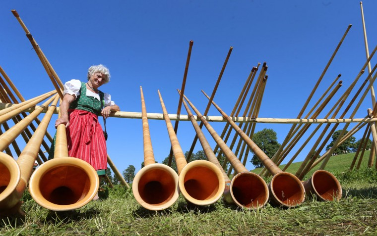 A woman in traditional Bavarian dress stands next to Alphorn instruments prior to a concert on August 28, 2016 in Nesselwang, southern Germany, during a mass performance of 300 alphorn blowers. (AFP PHOTO / dpa / Karl-Josef Hildenbrand)