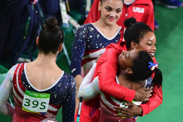 US gymnast Simone Biles (R) and US gymnast Gabrielle Douglas embrace during the women's team final Artistic Gymnastics at the Olympic Arena during the Rio 2016 Olympic Games in Rio de Janeiro on August 9, 2016. (Emmanuel Dunand/AFP/Getty Images)
