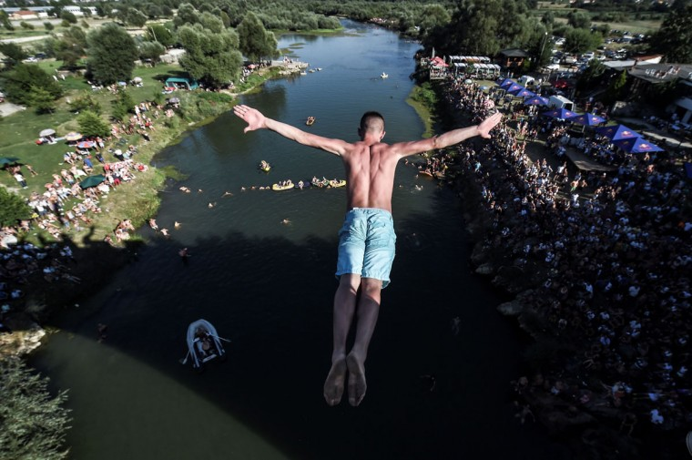 People look at a man as he jumps from the 22-meter-high bridge Ura during the High Diving competition near the town of Gjakova on July 31, 2016. (ARMEND NIMANI/AFP/Getty Images)