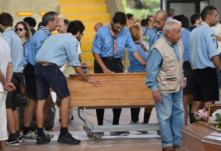 Italian boy scouts help to carry the coffins of earthquake victims, in a gymnasium arranged in a chapel of rest on August 26, 2016, in Ascoli Piceno, two day after a 6.2-magnitude earthquake struck the region killing some 267 people. Italy on August 26, 2016 declared a day of mourning for victims of a devastating earthquake as hopes of finding any more survivors dwindled and the confirmed death toll rose to 267. Flags will fly at half-mast across the country on August 27 to coincide with funerals for some of the victims. Immacolata Postiglione, head of the Civil Protection agency's emergency unit, said no new survivors had been found overnight in the remote mountain villages blitzed by the powerful pre-dawn quake on August 24, 2016. (Alberto Pizzoli/AFP/Getty Images)