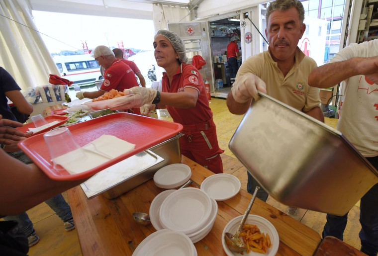 Italian Red Cross workers prepare meal for residents of earthquake affected areas in Amatrice on August 26, 2016, two day after a 6.2-magnitude earthquake struck the region killing some 267 people. An increasingly forlorn search for victims of the earthquake that brought carnage to central Italy entered a third day on August 26, 2016 as a day of mourning was declared for victims of a disaster that has claimed at least 267 lives. Releasing the new confirmed death toll, Immacolata Postiglione, head of the Civil Protection agency's emergency unit, indicated there had been no survivors found overnight in any of the remote mountain villages devastated by August 24's powerful pre-dawn quake. At least 367 people have been hospitalised with injuries but no one has been pulled alive from the piles of collapsed masonry since August 24 evening. (Andreas Solaro/AFP/Getty Images)