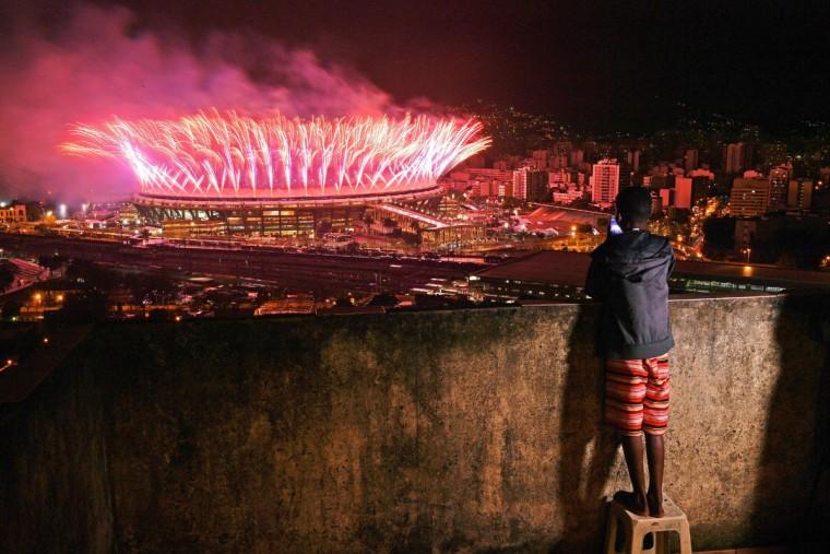 A boy from Mangueira favela watch fireworks over Maracana Stadium during the 2016 Olympics closing ceremony in Rio de Janeiro on August 21, 2016. (AFP PHOTO / CARL DE SOUZACARL DE SOUZA)