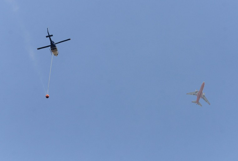 Firefighting air support pass in the air over Andrew Molera State Park as firefighters battle a wildfire in Big Sur on Thursday, Aug. 4, 2016. Officials say more than two dozen large wildfires are burning in the West. Hot, windy weather has made conditions difficult for firefighters as the blazes destroy homes and force evacuations. (David Royal/The Monterey County Herald via AP)