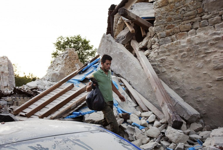 A man walks through rubble in Accumoli, central Italy, Friday, Aug. 26, 2016, two days after an earthquake. Strong aftershocks rattled residents and rescue crews alike Friday as hopes began to dim that rescuers would find any more survivors from Italy's earthquake. The first funerals were scheduled for some of the victims, with the government declaring a day of national mourning and a state funeral scheduled for Saturday. (Roberto Salomone/ANSA via AP)